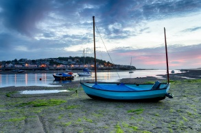 Sunset over a blue boat on the beach at Instow, looking out at the pretty fishing village of Appledore just outside of Bideford on the Devon coast